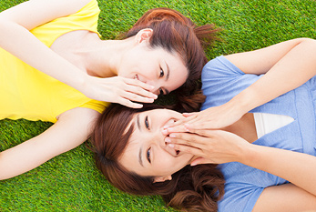 Two laughing girls are lying on a meadow on Best Friends Day.