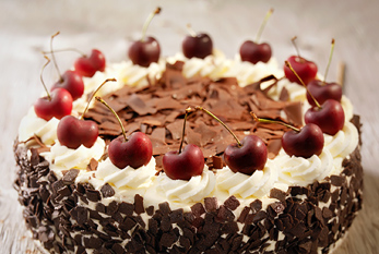 A Black Forest Cake on a wooden table.