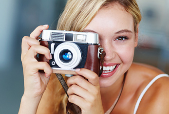 A blonde woman taking a picture with her camera.
