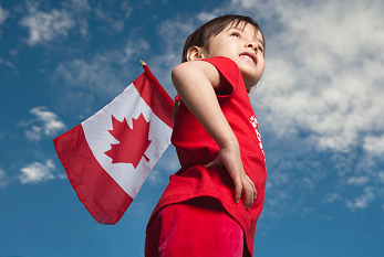 Young girl holding canadian flag on Canada Day.