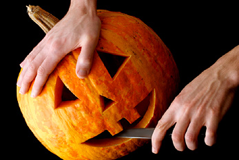 Male hands carving Halloween pumpkin