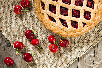 A cherry pie and single cherries.