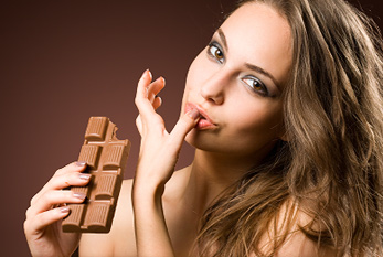 Young brunette woman tasting a bar of chocolate blocks.