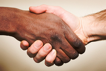 Shaking hands of two humans from different ethnic groups.