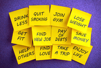 Sticky yellow note papers with a list of new year's resolutions on a bulletin board