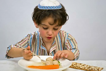 A jewish boy wearing a kippah on his head while eating matzah balls and unleavened bread.