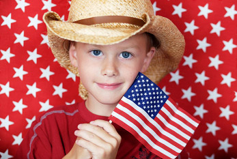 Boy with cowboy hat and US flag on Flag Day.