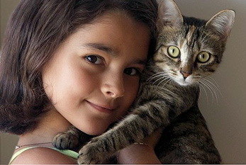 Young girl hugging a cat