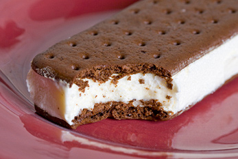 A bitten ice cream sandwich on a plate.
