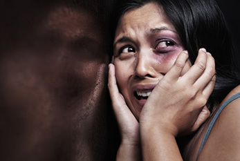 Abused woman terrified, leaning on a wooden wall.