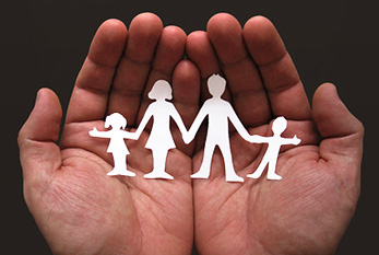 The family as a unit to be protected: paper silhouette of a family held by two hands.