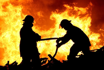 Silhouette of two firemen fighting a raging fire with huge flames.