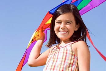 Young smiling girl with kite.