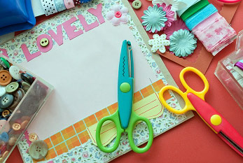 Different materials - such as scissors, paper and glue - at the workplace of a Scrapbooker.