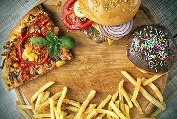 A junk food mix, showing pizza, a burger, a donut, and french fries.
