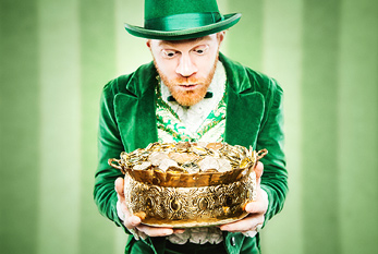 A leprechaun looking at his pot of gold.