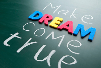 """Make your dream come true"" in colorful words on blackboard."