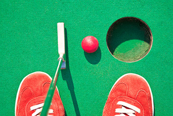 Miniatore golf hole with bat and ball.