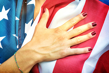 An American woman, putting her hand on her heart during the National Anthem.