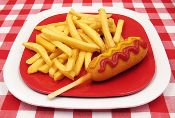 A corn dog with ketchup and mustard and a side of french fries.