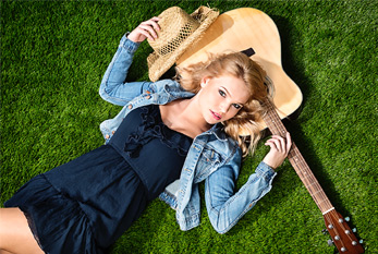 A young blonde country girl, lying in grass with a guitar.
