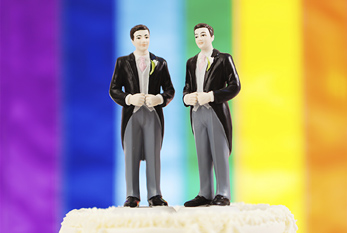 Two male figures on a wedding cake in front of a rainbow flag on National Freedom to Marry Day.