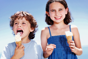 A boy and his sister enjoying their ice cream outside.