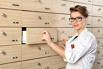 Young female pharmacist in front of drawers.