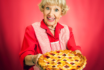 Grandmother holding a freshly baked lattice top cherry pie.