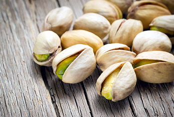 Pistachio nuts on wooden background.
