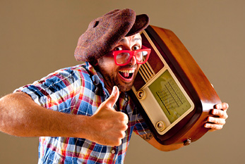 A funny man, listening to a radio he carries.