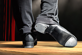 A man wearing tap dance shoes on stage.