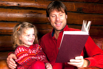 Story time: Father and daughter reading in a log cabin.