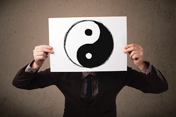 Man holding a yin-yang symbol in front of his head. Ying and Yang is used to describe how seemingly opposite or contrary forces are interconnected.