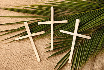 Palm crosses and real palm branches symbolizing Palm Sunday.