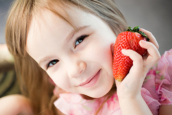 Girl with giant strawberry