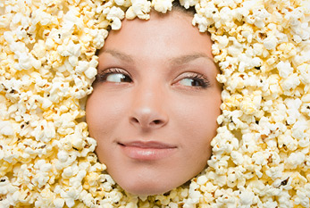 A popcorn lover: female covered in popcorn.