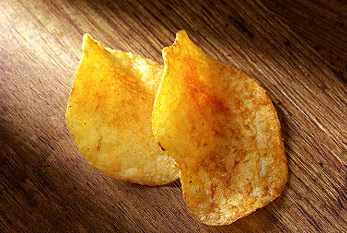 Two potato spicy chips in light beam.