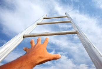 A man reaching up a ladder with blue sky in the background.
