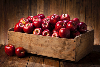 Red apples in a crate on a wooden table.