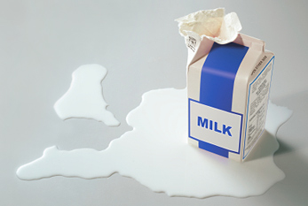 Carton of milk opened with spilt milk around it.