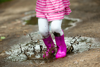 Little girl jumps into a puddle
