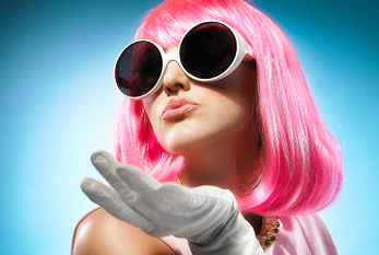 A young girl with big sun glasses und pink hairs.