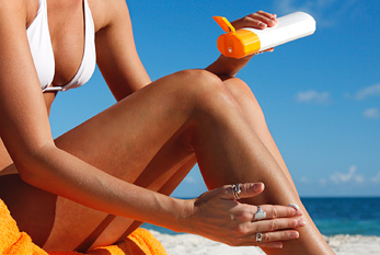 A woman putting on sunscreen on the beach.