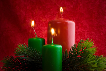 An Advent wreath with three burning candles.