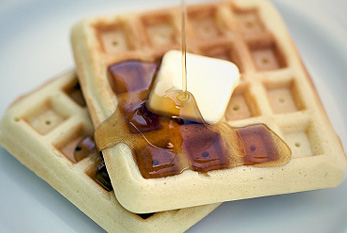 Syrup being poured onto delicious waffles.