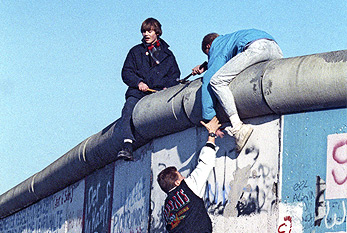 Young men climbing the Berlin Wall on November 1989.