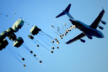 An airplane airdrops pallets of water and food over a disaster area.