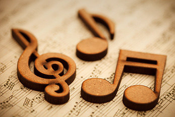Wooden musical notes on an old sheet of music.